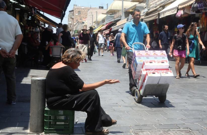 A woman begs in Jerusalem (photo credit: MARC ISRAEL SELLEM/THE JERUSALEM POST)