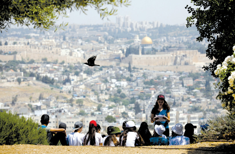A CROW flies past as schoolchildren gather at a look-out point on the Armon Hanatziv Promenade in Jerusalem (photo credit: AMIR COHEN/REUTERS)