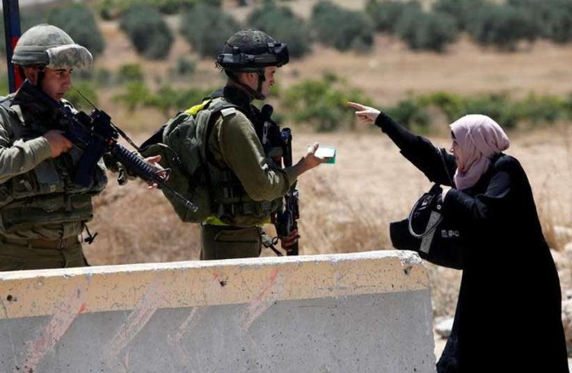 A Palestinian woman argues with Israeli army soldiers as she is searched at a checkpoint during clashes in the West Bank Al-Fawwar refugee camp, south of Hebron (photo credit: REUTERS/MUSSA QAWASMA)