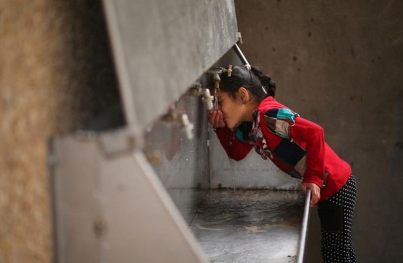 A Palestinian girl drinks from a public tap at the Jabaliya refugee camp in the Gaza Strip (photo credit: MOHAMMED SALEM/ REUTERS)