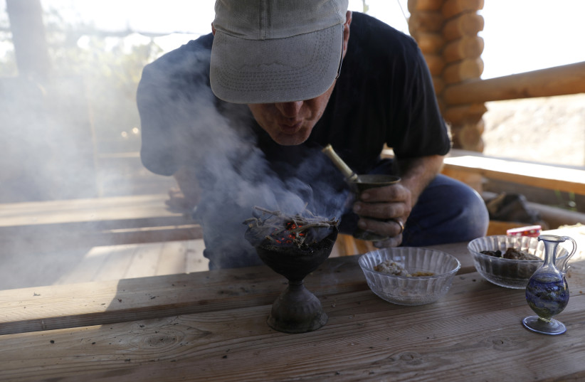 Guy Erlich, an Israeli entrepreneur, demonstrates the burning of dried and crushed resins of three plants, frankincense, myrrh and Balsam of Gilead in Kibbutz Almog, Judean desert, in the West Bank (photo credit: REUTERS)
