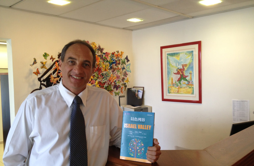 Israeli private equity investor Edouard Cukierman holds up a book he co-authored that was translated into Mandarin in 2014. Cukierman is focusing evermore on Chinese investment into Israel (photo credit: Courtesy)