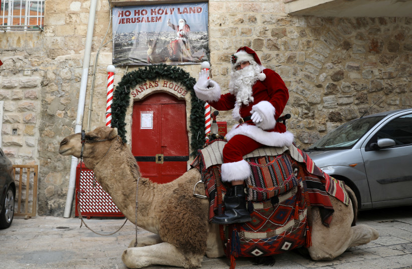 Issa Kassissieh, wearing a Santa Claus costume, rides a camel during the annual Christmas tree distribution by the Jerusalem municipality in Jerusalem's Old City December 21, 2017 (photo credit: AMMAR AWAD/REUTERS)