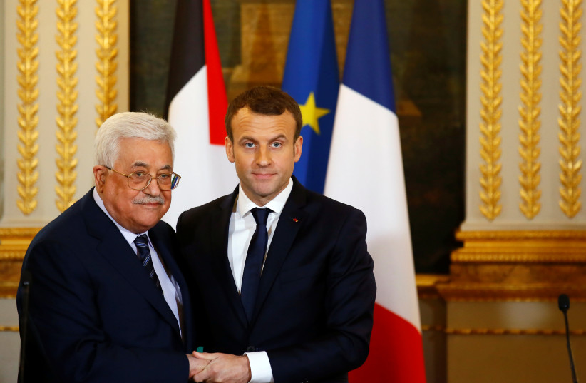 French President Emmanuel Macron (R) and Palestinian President Mahmoud Abbas deliver a press statement after a meeting at the Elysee Palace in Paris, France, December 22, 2017. (photo credit: REUTERS)