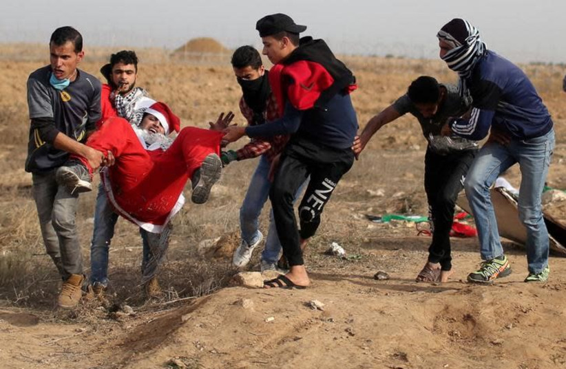 "A wounded Palestinian demonstrator dressed as Santa Claus is evacuated during clashes with Israeli troops, at a protest as Palestinians call for a ""Day of Rage"" in response to US President Donald Trump's recognition of Jerusalem as Israel's capital, near the border with Israel in the southern Gaza  (photo credit: REUTERS/IBRAHEEM ABU MUSTAFA)"