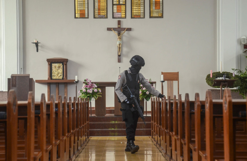 An Indonesian bomb squad policeman holds a rifle as he examines a church before Christmas mass prayer in Bandung, Indonesia, December 23, 2017 in this photo taken by Antara Foto. Picture taken December 23, 2017 (photo credit: ANTARA FOTO/RAISAN AL FARISI/VIA REUTERS)