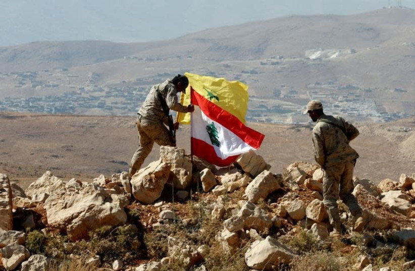 Hezbollah fighters put Lebanese and Hezbollah flags at Juroud Arsal, Syria-Lebanon border, July 25, 2017 (photo credit: REUTERS/MOHAMED AZAKIR)