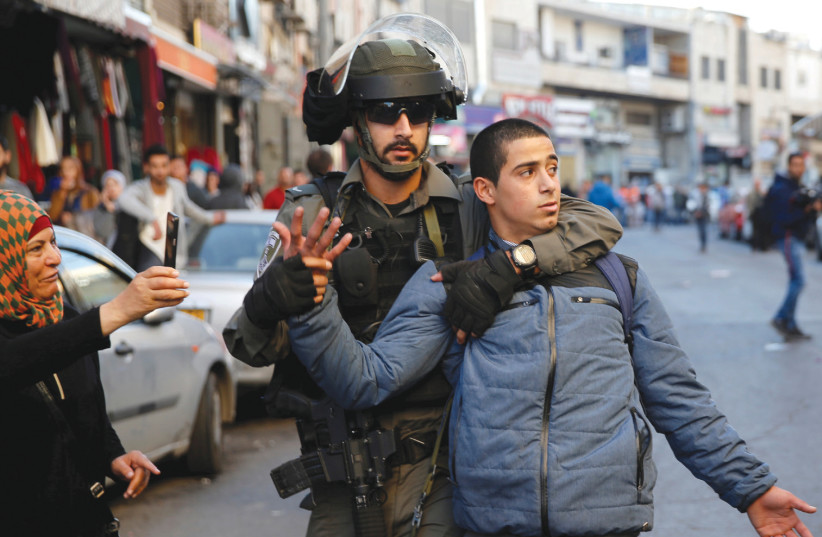 An Israeli border police officer detains a Palestinian protester during a demonstration in east Jerusalem on December 16 (photo credit: AMMAR AWAD/REUTERS)