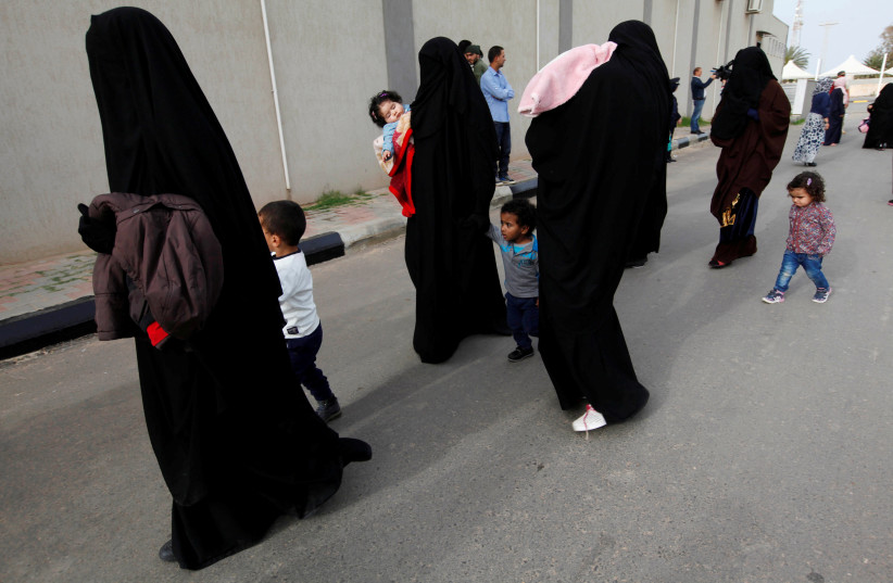 Female jihadists walk with their children at Reform and Rehabilitation foundation in Mitiga in Tripoli, Libya. (photo credit: REUTERS)