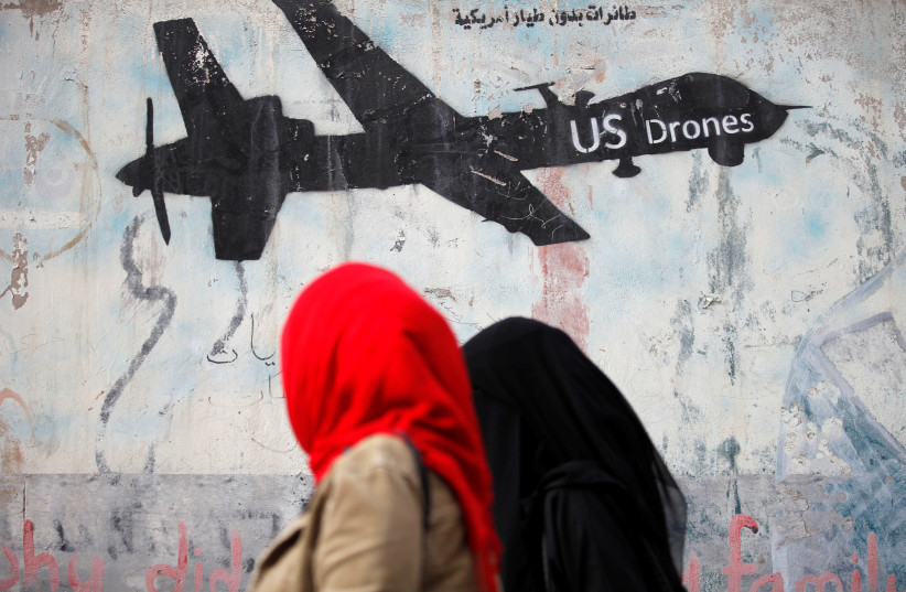 Women walk past a graffiti, denouncing strikes by US drones in Yemen, painted on a wall in Sanaa, Yemen. (photo credit: REUTERS)