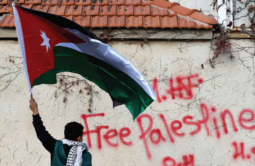 A BOY holds the Jordanian national flag during a protest near the US Embassy in Amman, Jordan. (photo credit: REUTERS)