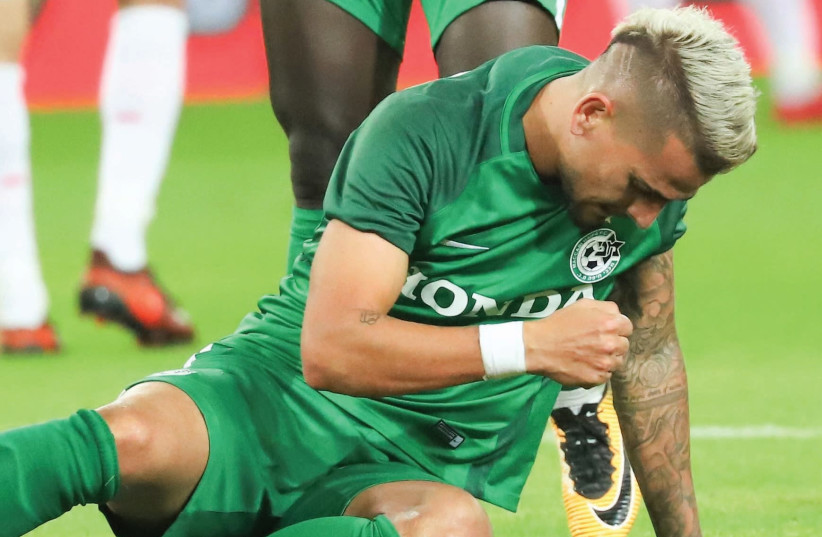 Maccabi Haifa midfielder Maor Buzaglo thumped the ground in frustration night after re-injuring his right knee, one month after coming back from a seven-month layoff (photo credit: DANNY MAROM)