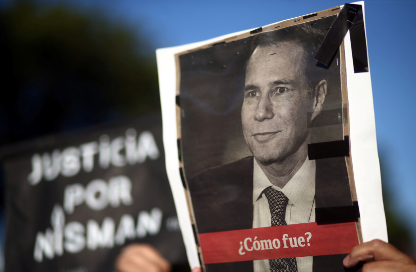 A woman holds up a photo of late state prosecutor Alberto Nisman, lead investigator into the car bomb attack that killed 85 people at a Buenos Aires' Jewish community center, during commemorations of the second anniversary of his death in Buenos Aires, Argentina, January 18, 2017. (photo credit: REUTERS)