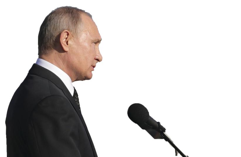 RUSSIAN PRESIDENT Vladimir Putin addresses servicemen as he visits the Hmeymim air base in Latakia Province, Syria (photo credit: MIKHAIL KLIMENTYEV/SPUTNIK/REUTERS)