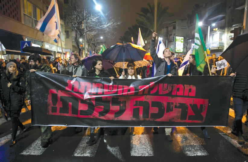 PROTESTERS CALL for the resignation of Prime Minister Benjamin Netanyahu over police investigations for suspected corruption at a demonstration in Tel Aviv in January. The banner says 'A corrupt government must go.' (photo credit: BAZ RATNER/REUTERS)
