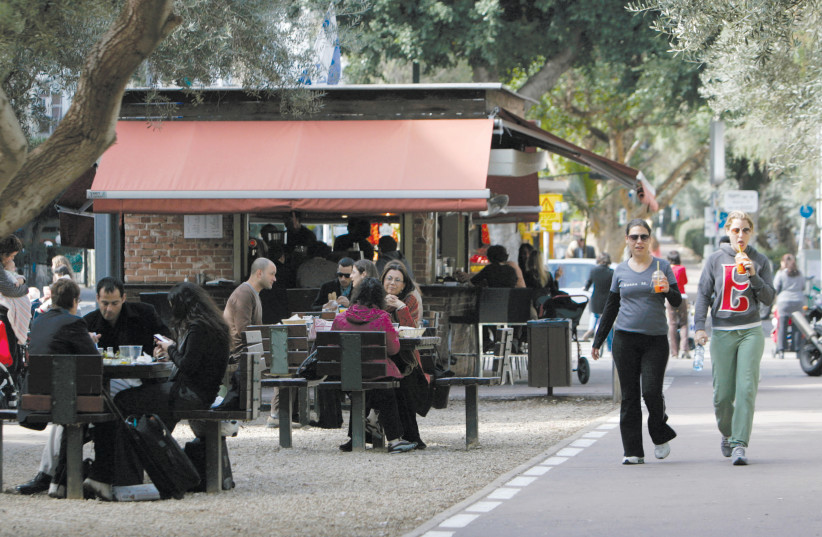 PEOPLE WALK past a cafe in Tel Aviv (photo credit: SHARON PERRY/REUTERS)