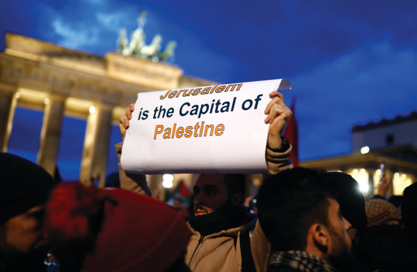 A PROTESTER holds a placard during the demonstration outside the US embassy in Berlin against President Donald Trump's decision to recognize Jerusalem as Israel's capital (photo credit: AXEL SCHMIDT/REUTERS)