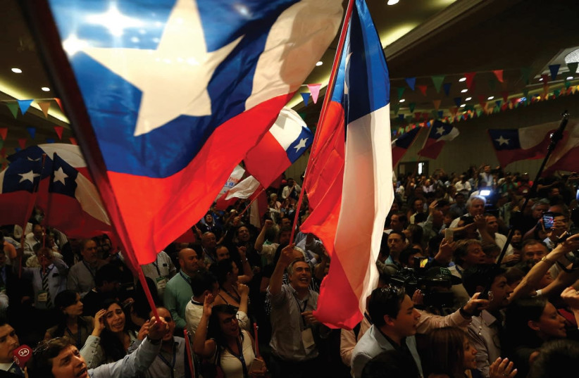 CHILEANS RAISE their flag during a political campaign earlier this month.  (photo credit: REUTERS)