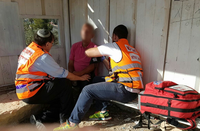 Psycho-trauma and Crisis Response Unit volunteers aid an Israeli suffering from shock (photo credit: UNITED HATZALAH)