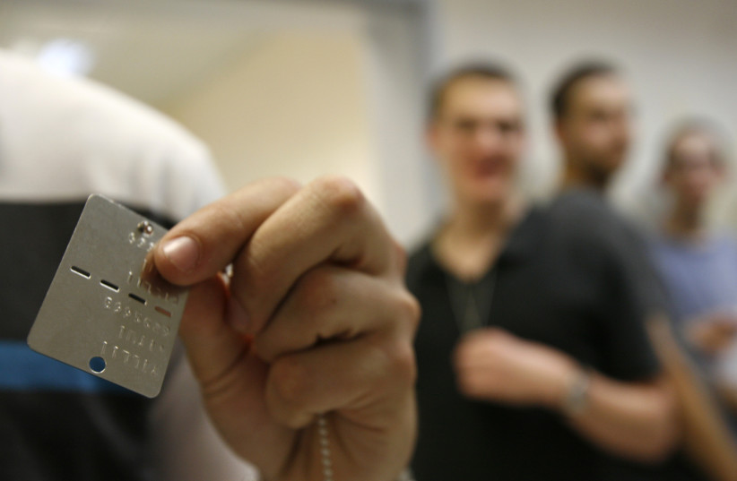 A conscript displays his identifying dog tag at the Tel Hashomer Israel Defence Forces (IDF) Recruitment Center near Tel Aviv March 14, 2010. (photo credit: REUTERS)