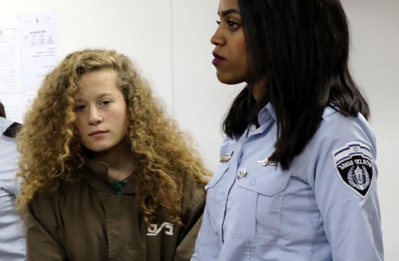 Palestinian teen Ahed Tamimi enters a military courtroom escorted by Israeli Prison Service personnel at Ofer Prison near the West Bank city of Ramallah, December 28, 2017.  (photo credit: AMMAR AWAD / REUTERS)
