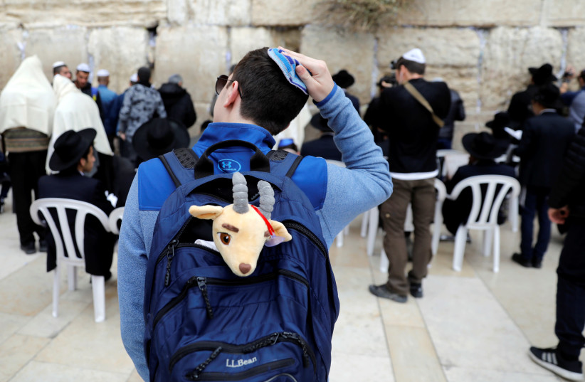 A man stands in front of the Western Wall during a special prayer for rain in Jerusalem's Old City, December 28, 2017. (photo credit: RONEN ZVULUN / REUTERS)