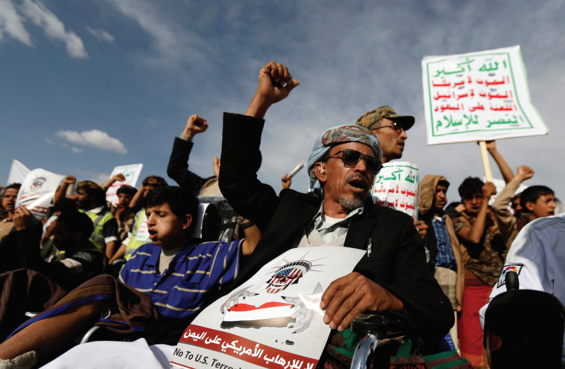 """HOUTHI FOLLOWERS in Sanaa, Yemen demonstrate against US President Donald Trump's visit to neighboring Saudi Arabia in May. Their placards slam Israel, too: """"Allah is the greatest. Death to America, death to Israel, a curse on the Jews, victory to Islam"""". (photo credit: KHALED ABDULLAH/ REUTERS)"""