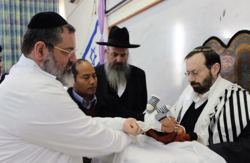 MICHAEL FREUND serves as the 'sandak' or godfather at the circumcision ceremony for Ovadiah Daniel Lunghel. (photo credit: Courtesy)