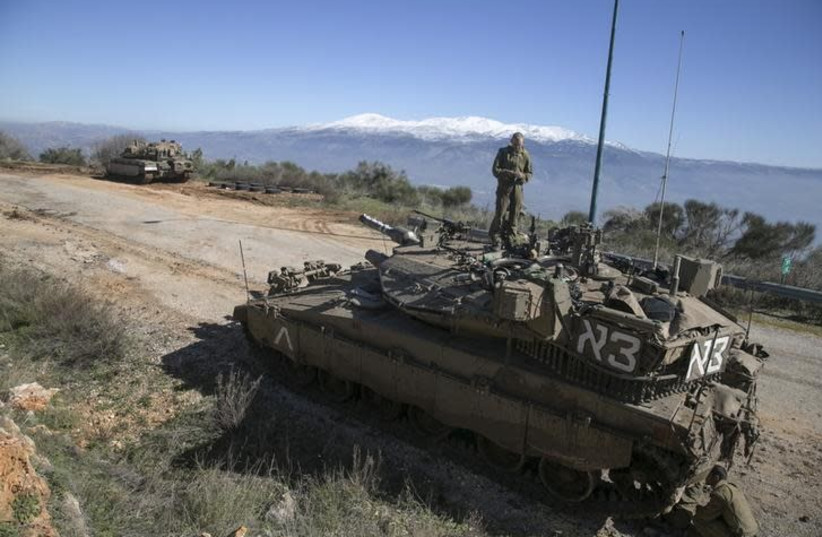 An Israeli soldier stands atop a tank near Israel's border with Lebanon January 21, 2015 (photo credit: REUTERS/BAZ RATNER)