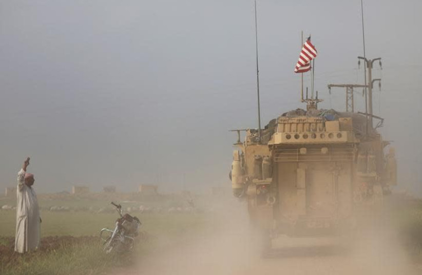 A man gestures at US military vehicles driving in the town of Darbasiya next to the Turkish border, Syria, April 2017 (photo credit: REUTERS/RODI SAID)