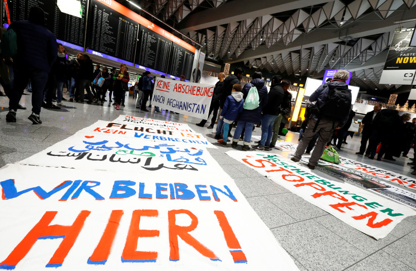 """Protestors display placards reading """"We stay here"""", """"No deportation to Afghanistan"""" and """"Fleeing is not a crime"""" as they demonstrate against the deportation of people to Afghanistan at Fraport airport in Frankfurt, Germany (photo credit: REUTERS/KAI PFAFFENBACH)"""