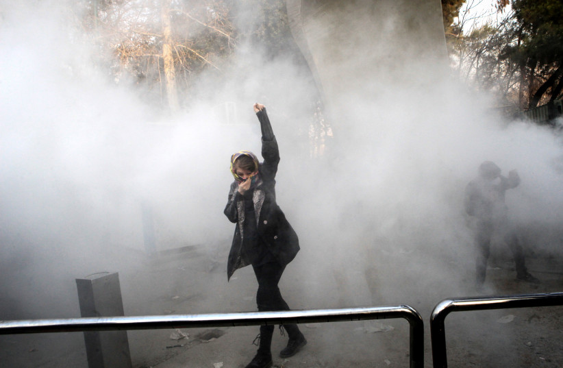 An Iranian woman raises her fist amid the smoke of tear gas at the University of Tehran during a protest on December 30, 2017 (photo credit: STR / AFP)