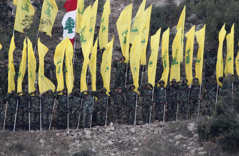 HEZBOLLAH MEMBERS wave Hezbollah and Lebanese flags during a 2015 rally in southern Lebanon marking the anniversary of the end of the terrorist organization's 2006 war with Israel.  (photo credit: AZIZ TAHER/REUTERS)