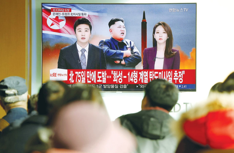 PEOPLE IN SEOUL watch a TV news report on North Korea's launch of an ICBM that landed close to Japan last November (photo credit: KIM HONG/ REUTERS)