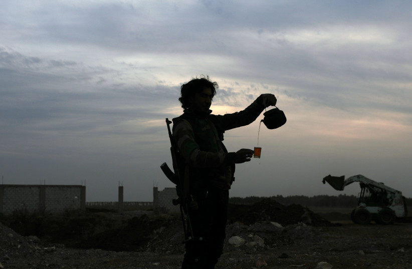 A Free Syrian army fighter pours tea in the rebel-held town of Dael, Syria. (photo credit: REUTERS)