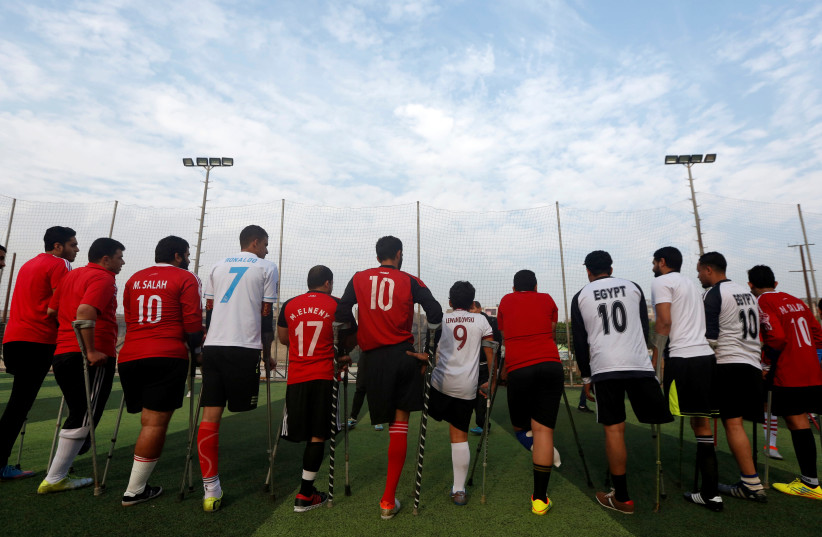 """Members of """"Miracle Team"""", a soccer team made up of one-legged soccer players, listen to their coach before a training session at El Salam club on the outskirts of Cairo (photo credit: AMR ABDALLAH DALSH / REUTERS)"""