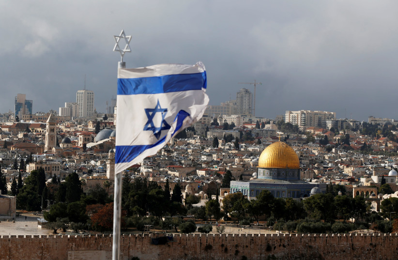 An Israeli flag is seen near the Dome of the Rock, located in Jerusalem's Old City  (photo credit: AMMAR AWAD / REUTERS)