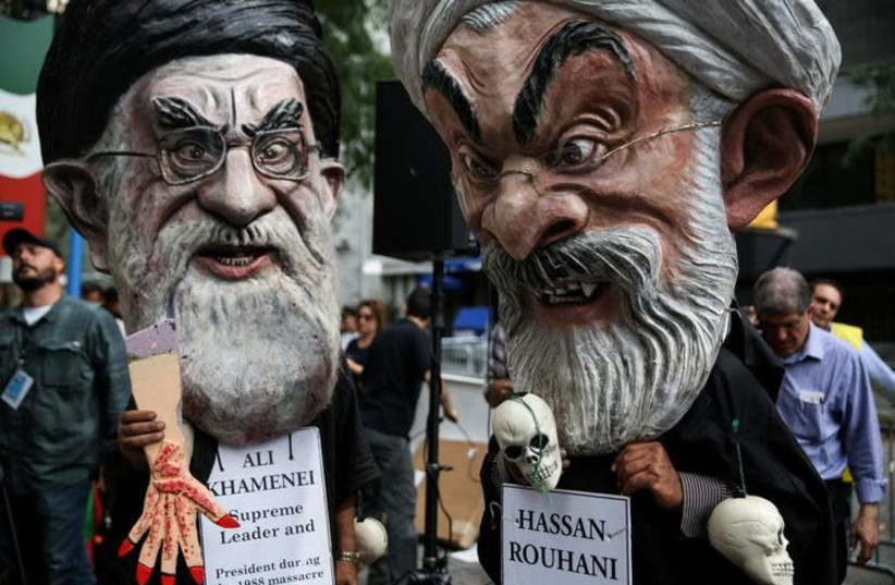 Iranian Americans and opponents of Iranian President Hassan Rouhani hold protests outside of UN headquarters on the day Rouhani addresses the General Assembly of the United Nations in New York, US, September 20, 2017. (File Photo) (photo credit: REUTERS/AMR ALFIKY)