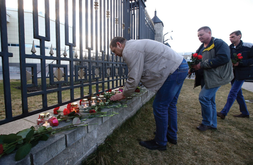 Men lay flowers at a cemetery to commemorate victims of the St. Petersberg metro blast (photo credit: REUTERS)