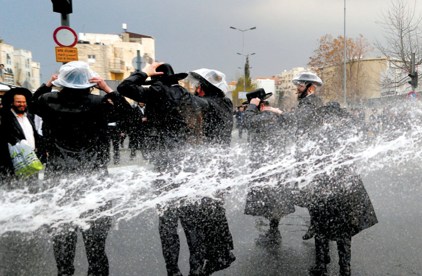 HAREDI protesters are sprayed with water by police as they block a street during a demonstration in Jerusalem against members of their community serving in the IDF, part of ongoing demonstrations (photo credit: AMMAR AWAD/REUTERS)