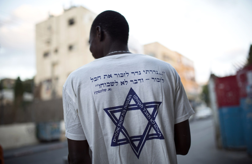 """An African migrant wears a T-shirt with a Hebrew phrase referring to the Holocaust,"""" I promise to remember... and never forget!"""" in south Tel Aviv July 17, 2013. (photo credit: REUTERS)"""