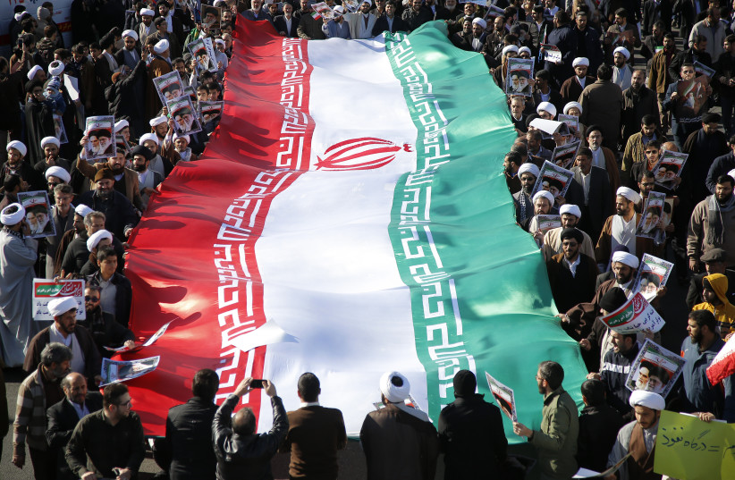 Pro-government demonstrators wave their national flag during a march in Iran's holy city of Qom, some 130 kilometres south of Tehran, on January 3, 2018 (photo credit: AFP PHOTO)