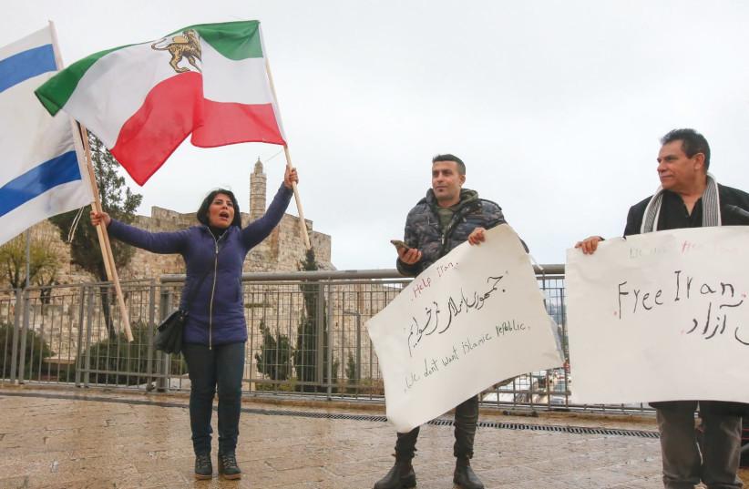 L'IRANIAN BLOGGER et la militante des droits humains Neda Amin, agitant l'ancien drapeau iranien et le drapeau israélien, dirigent mardi un petit rassemblement à Jérusalem en solidarité avec les manifestants en Iran. (crédit photo: MARC ISRAEL SELLEM / THE JERUSALEM POST)