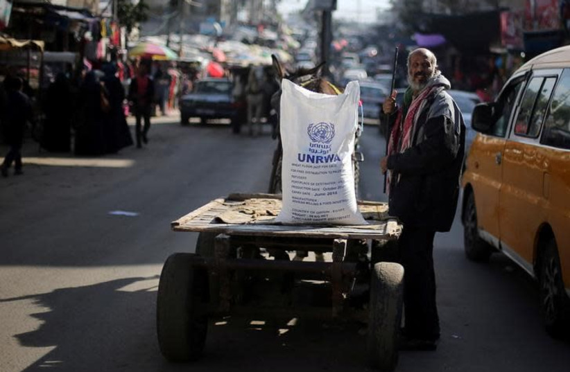 A Palestinian man stands next to a cart carrying a flour sack distributed by the United Nations Relief and Works Agency (UNRWA) in Khan Younis refugee camp in the southern Gaza Strip January 3, 2018 (photo credit: REUTERS/IBRAHEEM ABU MUSTAFA)