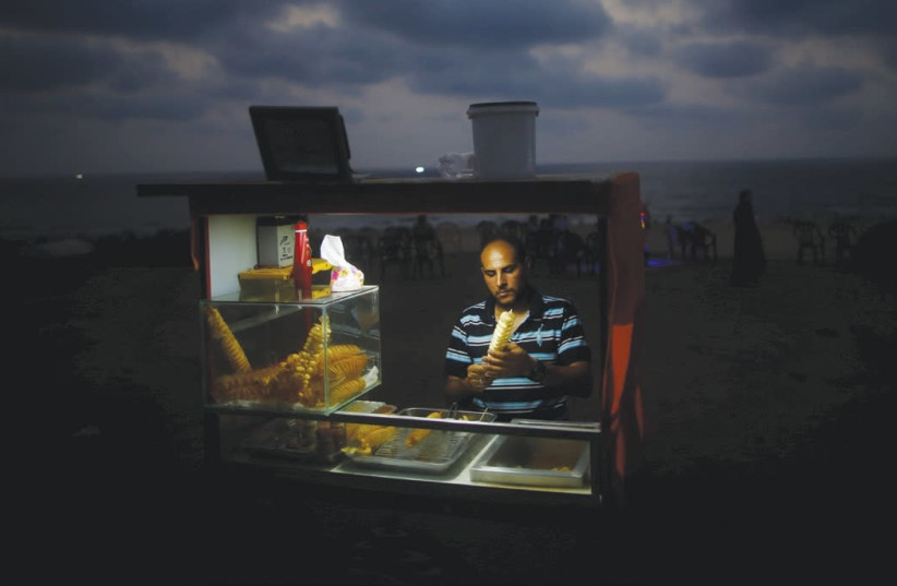 A vendor sells snacks on a beach during a power cut in Gaza City in summer of 2017 (photo credit: MOHAMMED SALEM/REUTERS)