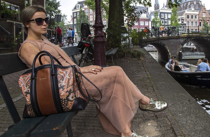 """Victoria Koblenko, 33, poses on the bench which was used in the movie """"The Fault In Our Stars"""", in Amsterdam July 11, 2014. (photo credit: REUTERS)"""