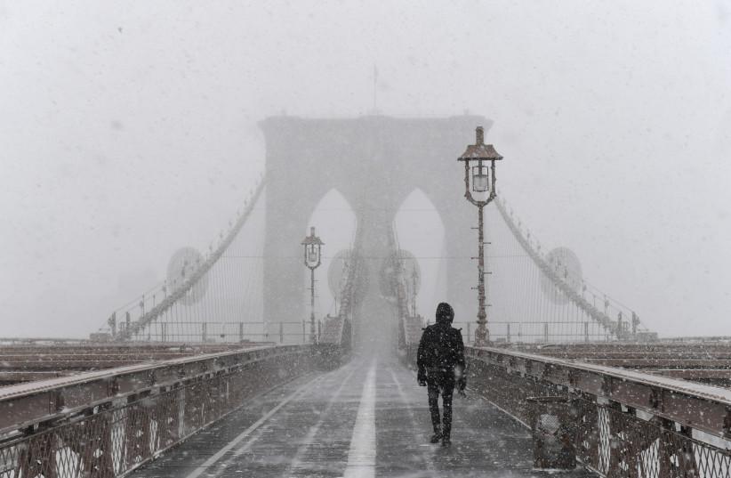 A pedestrian walks through blinding snow across the Brooklyn Bridge during Storm Grayson in New York City, U.S., January 4, 2018. (photo credit: REUTERS)
