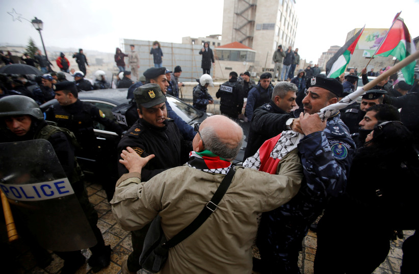 Palestinian security forces push away demonstrators from the convoy of Greek Orthodox Patriarch of Jerusalem Theophilos III, during a protest against his visit, in the West Bank city of Bethlehem. (photo credit: REUTERS)