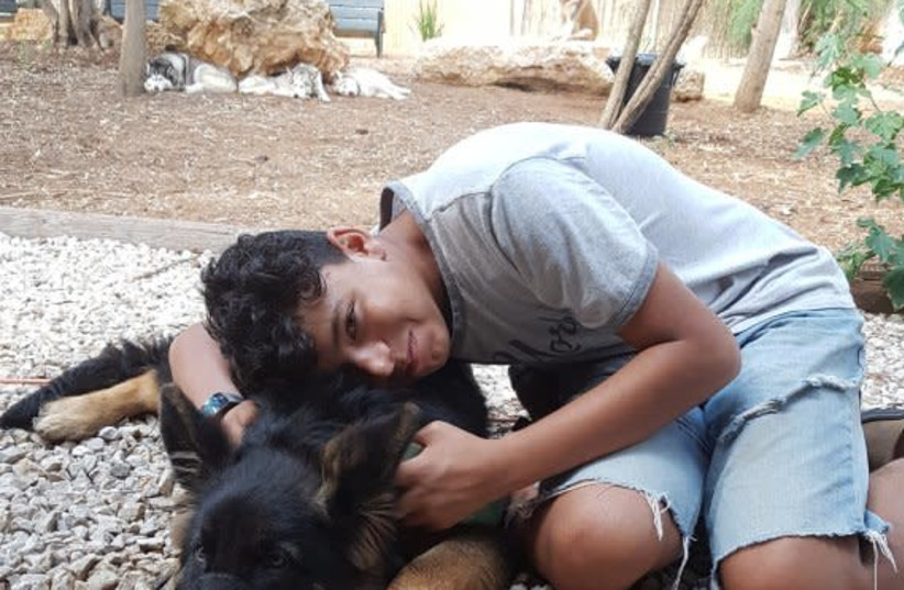 Lidor, a member of the Hadassah Ne'urim Youth village, poses with one of the dogs being rehabilitated at the site. (photo credit: Courtesy)