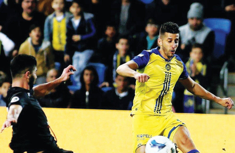 Two days after signing a four-year contract extension, Maccabi Tel Aviv midfielder Dor Micha (right) set up his team's opener in last night's 3-0 victory over Bnei MMBE in the State Cup round-of-32. (photo credit: ADI AVISHAI)